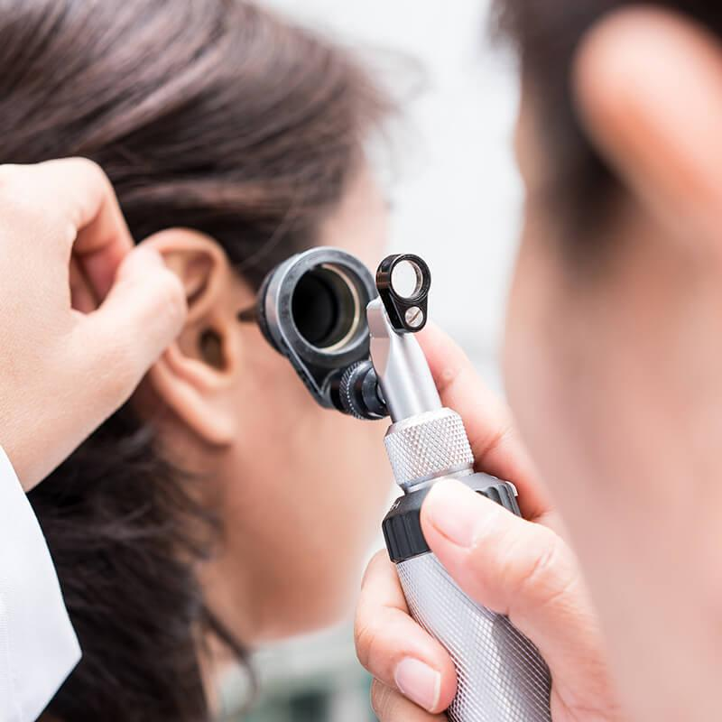examining a patient's ear with an otoscope